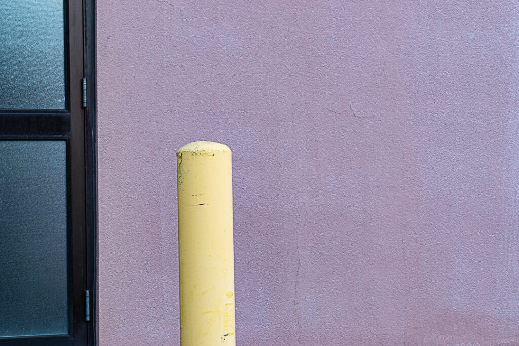 Yellow pole against pink building