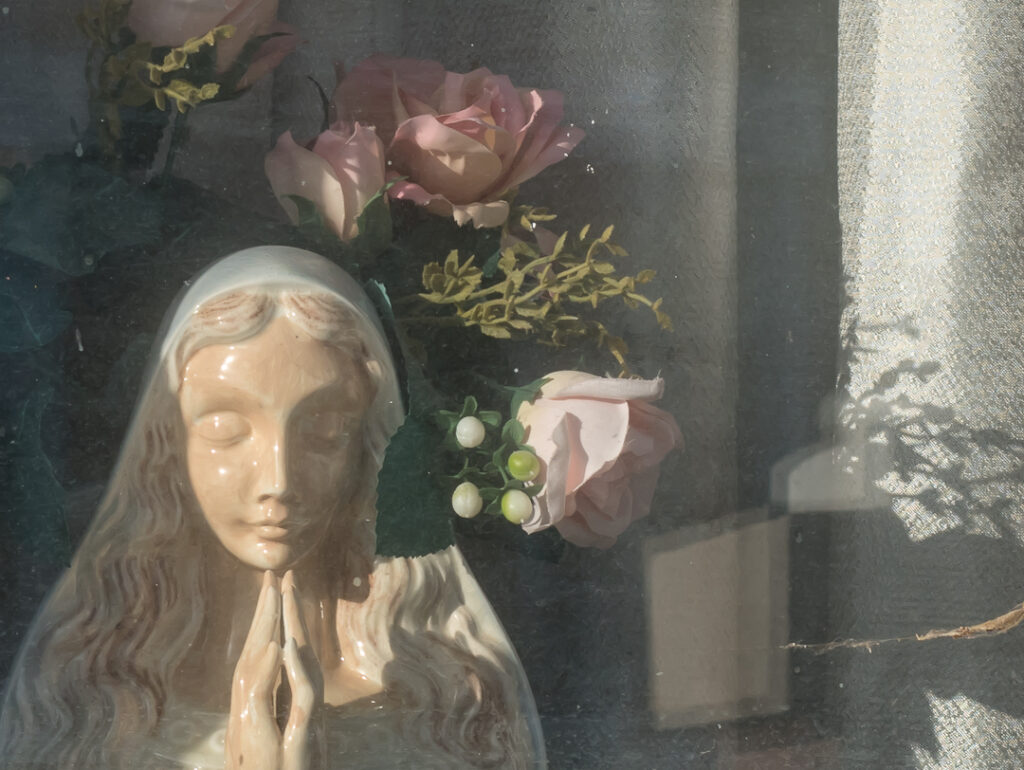 Window with roses, statue, and curtains