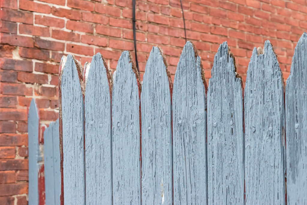 Fence with cracked blue paint with a background of red brick.
