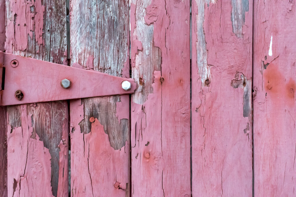 A red fence with peeling paint