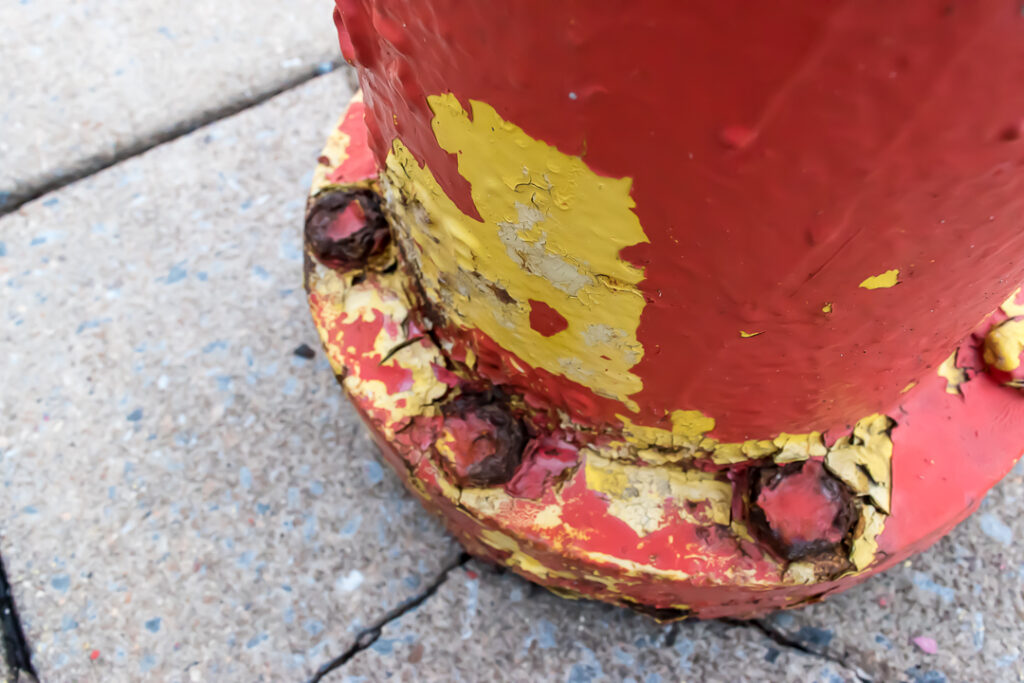 Peeling red and yellow paint on the base of a fire hydrant